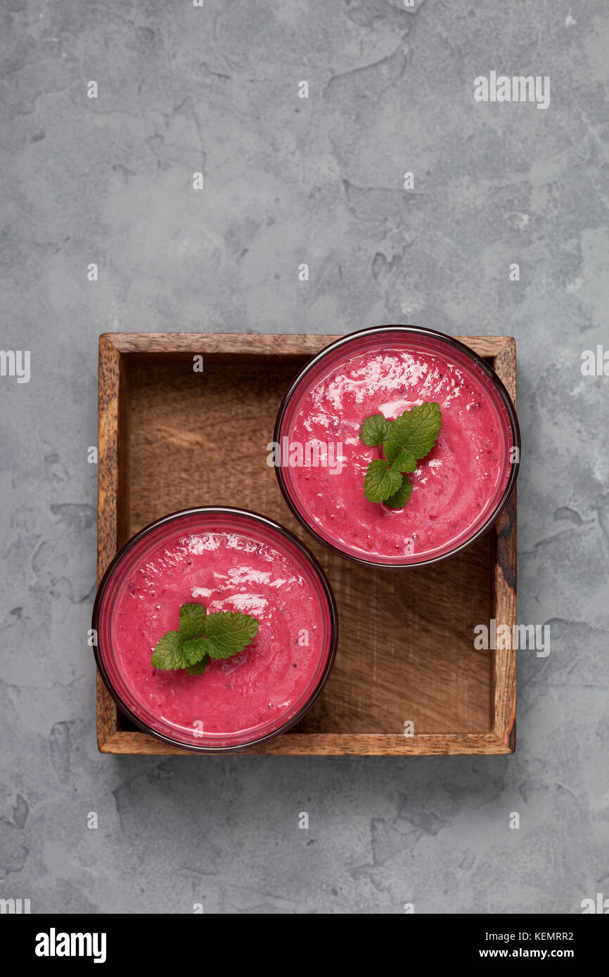 red berry fruit smoothies in glasses on a gray concrete background. view from above. copy space - Stock Image