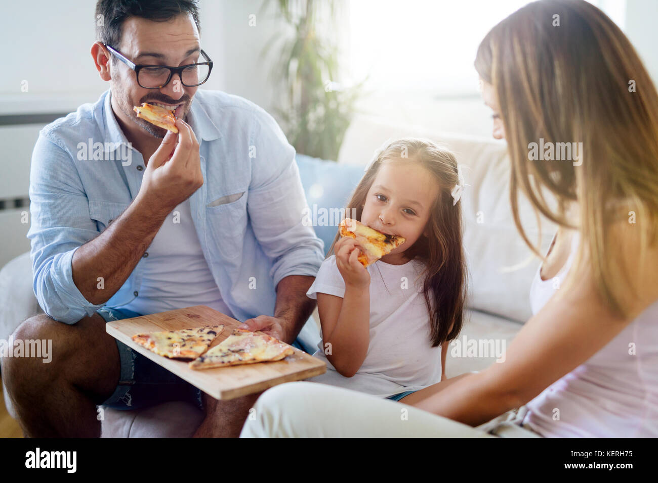 Happy family sharing pizza together at home - Stock Image