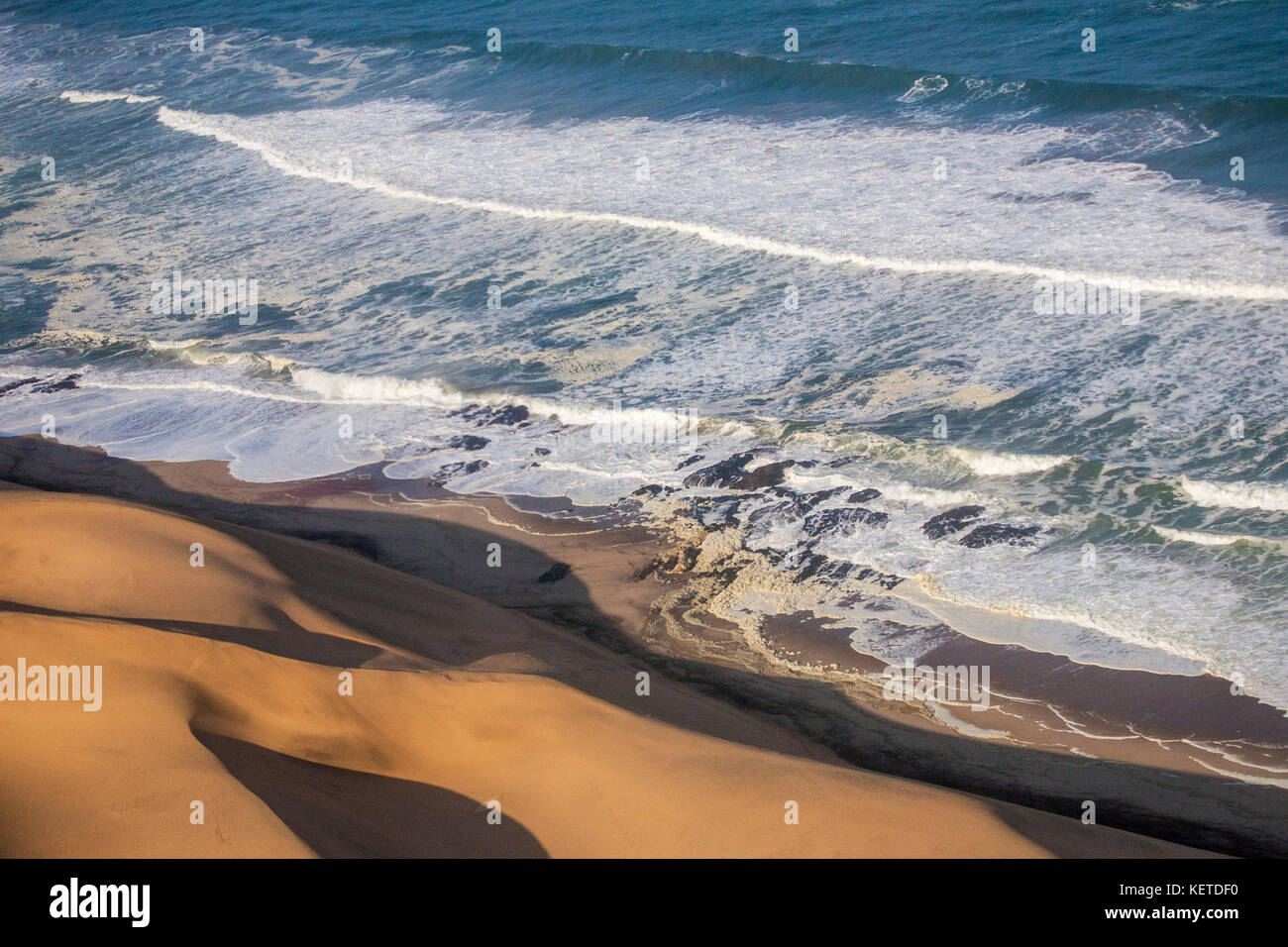 Aerial view of waves of the Atlantic Ocean crashing against the sandy dunes of the Namib desert Namibia Southern - Stock Image