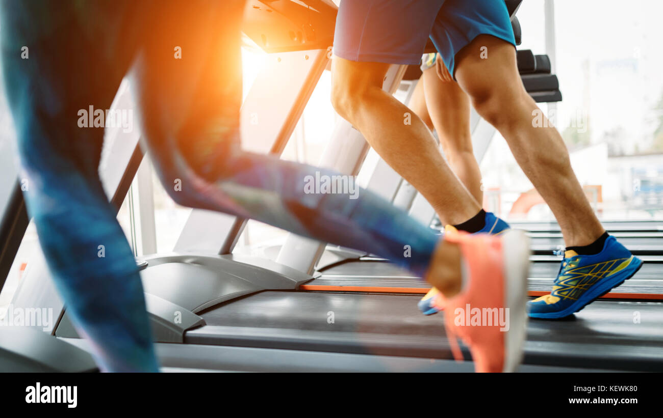Picture of people running on treadmill in gym - Stock Image