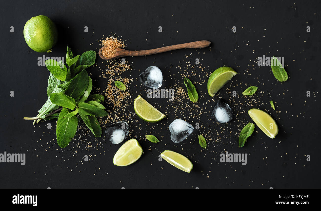 Ingredients for mojito. Fresh mint, limes, ice, sugar over black backdrop - Stock Image