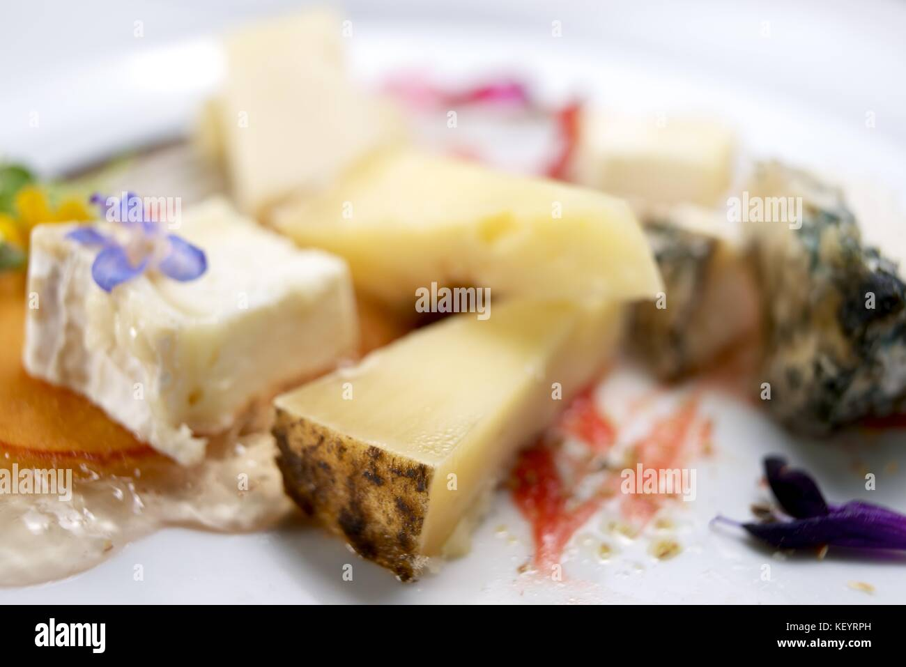 Lots of assorted cheese on a white table. - Stock Image