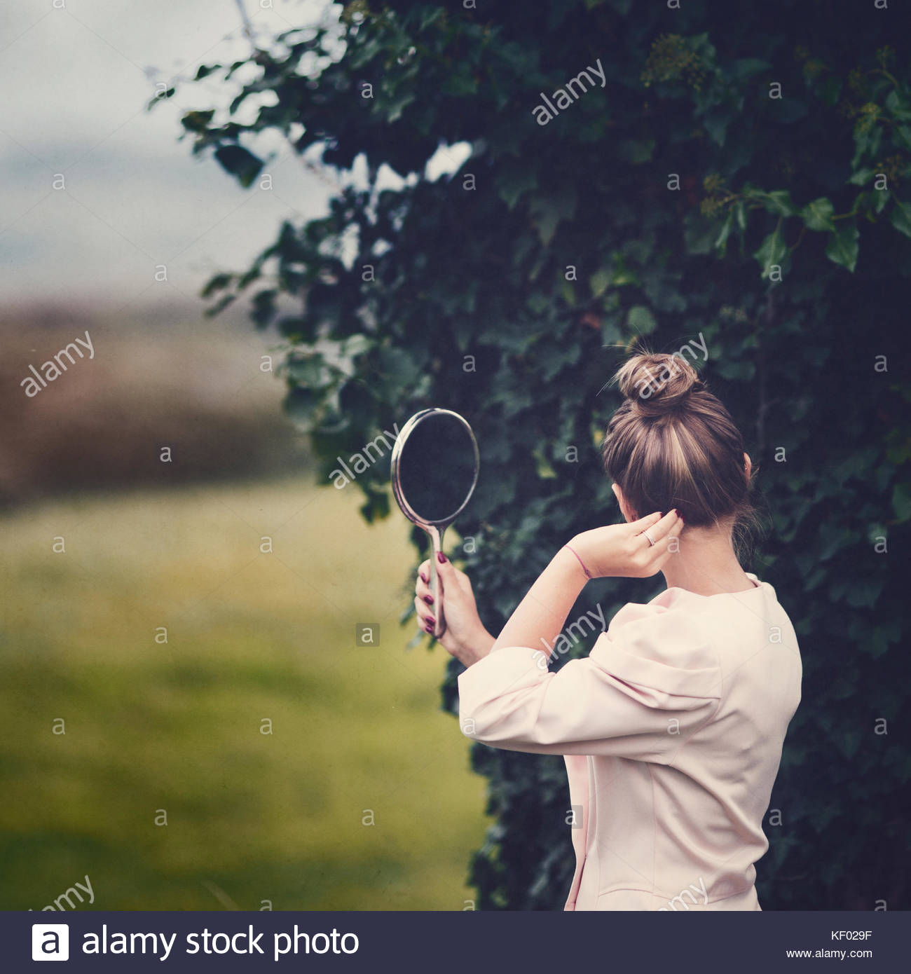 Girl holding a mirror, looking at herself. - Stock Image