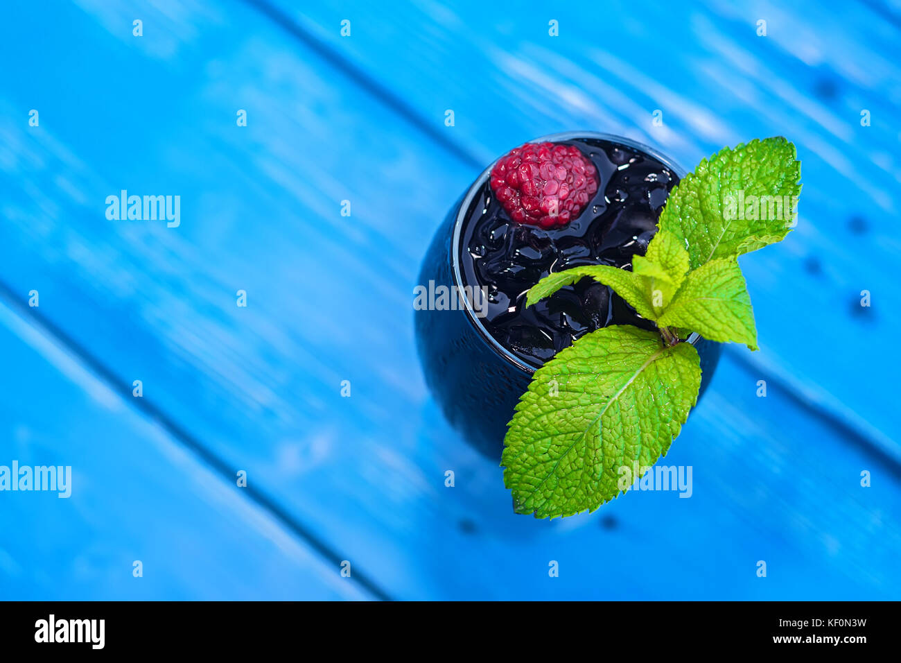 Dark restaurant cocktail with mint and raspberry - Stock Image