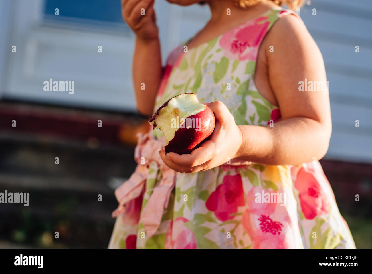 2-3 year old holding half eaten apple. - Stock Image
