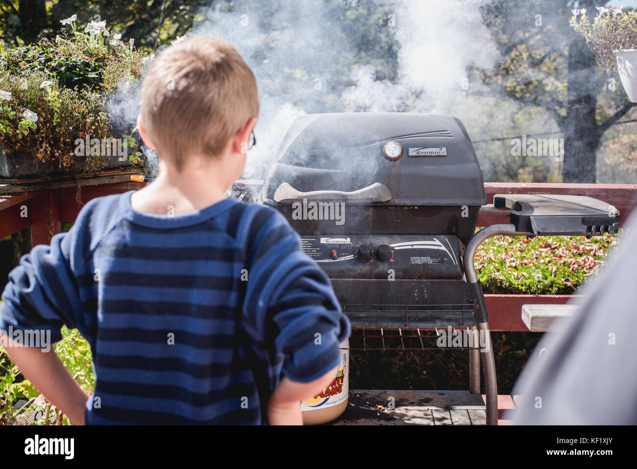 10-year old boy looking at grill with smoke - Stock Image