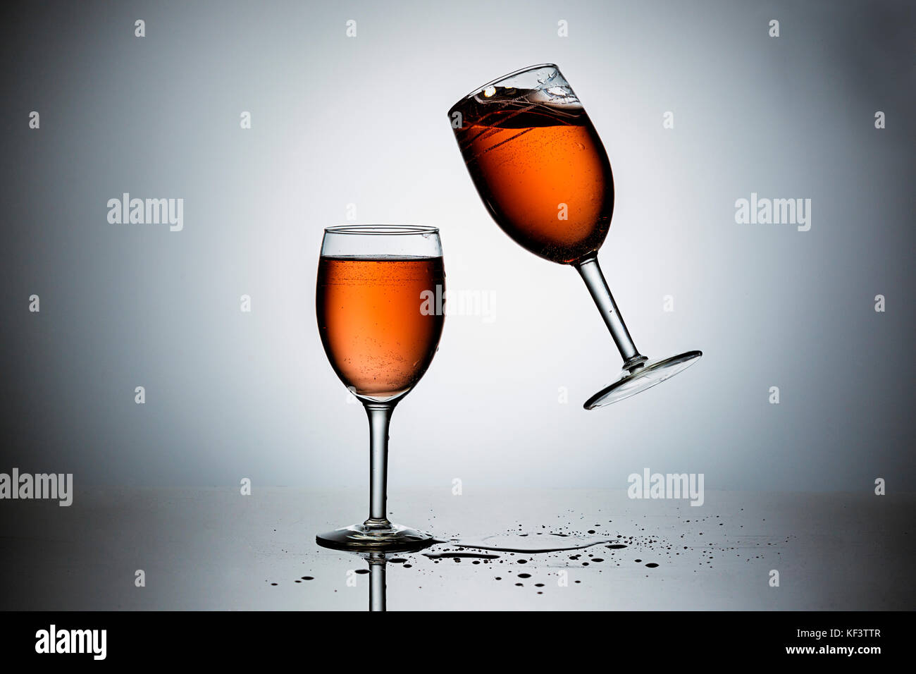 Dropping a wineglass filled with wine onto another. - Stock Image