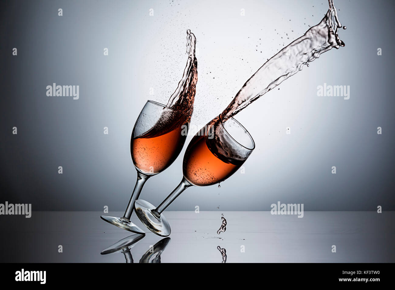 The movement of sliding one wine glass filled with wine into another one. - Stock Image