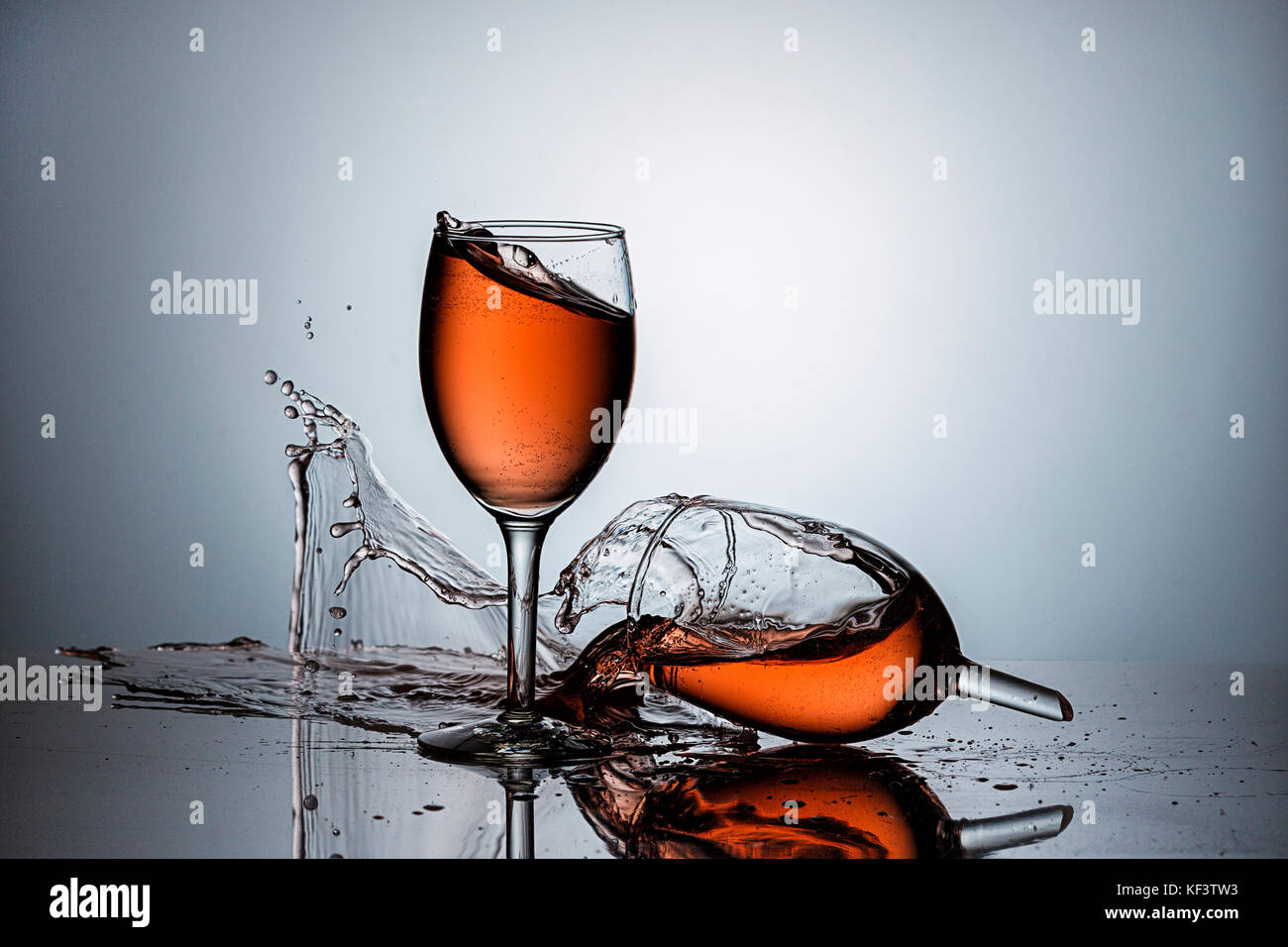 A broken wine glass spills wine after being dropped. - Stock Image