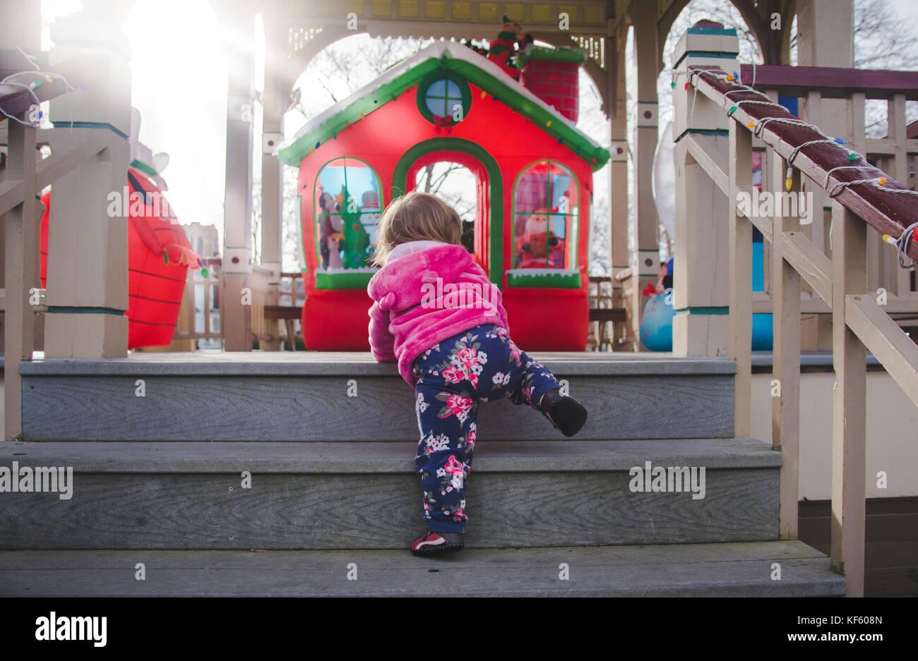 Toddler walking toward Christmas or holiday displays. - Stock Image