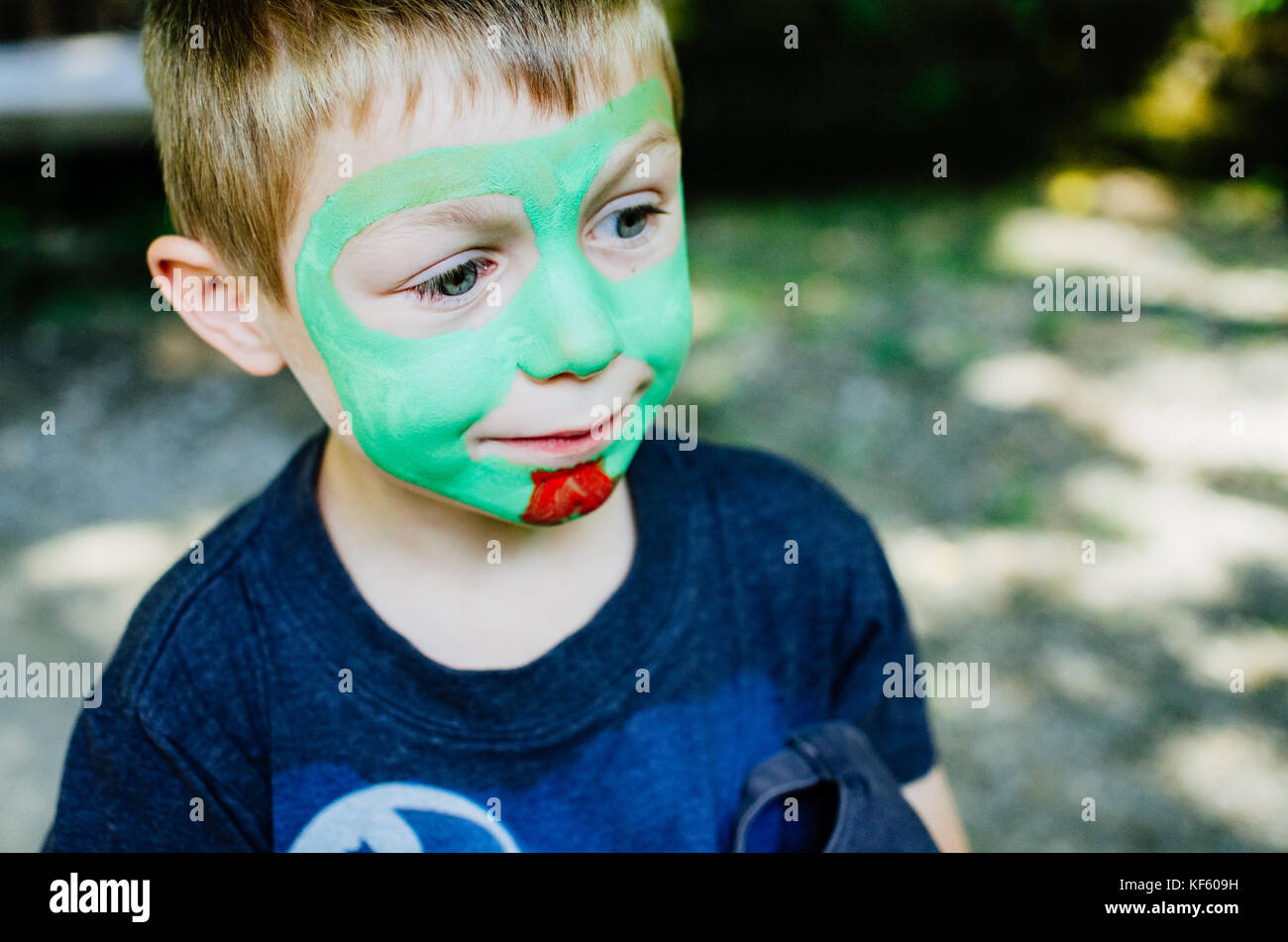A boy with green face paint being painted - Stock Image