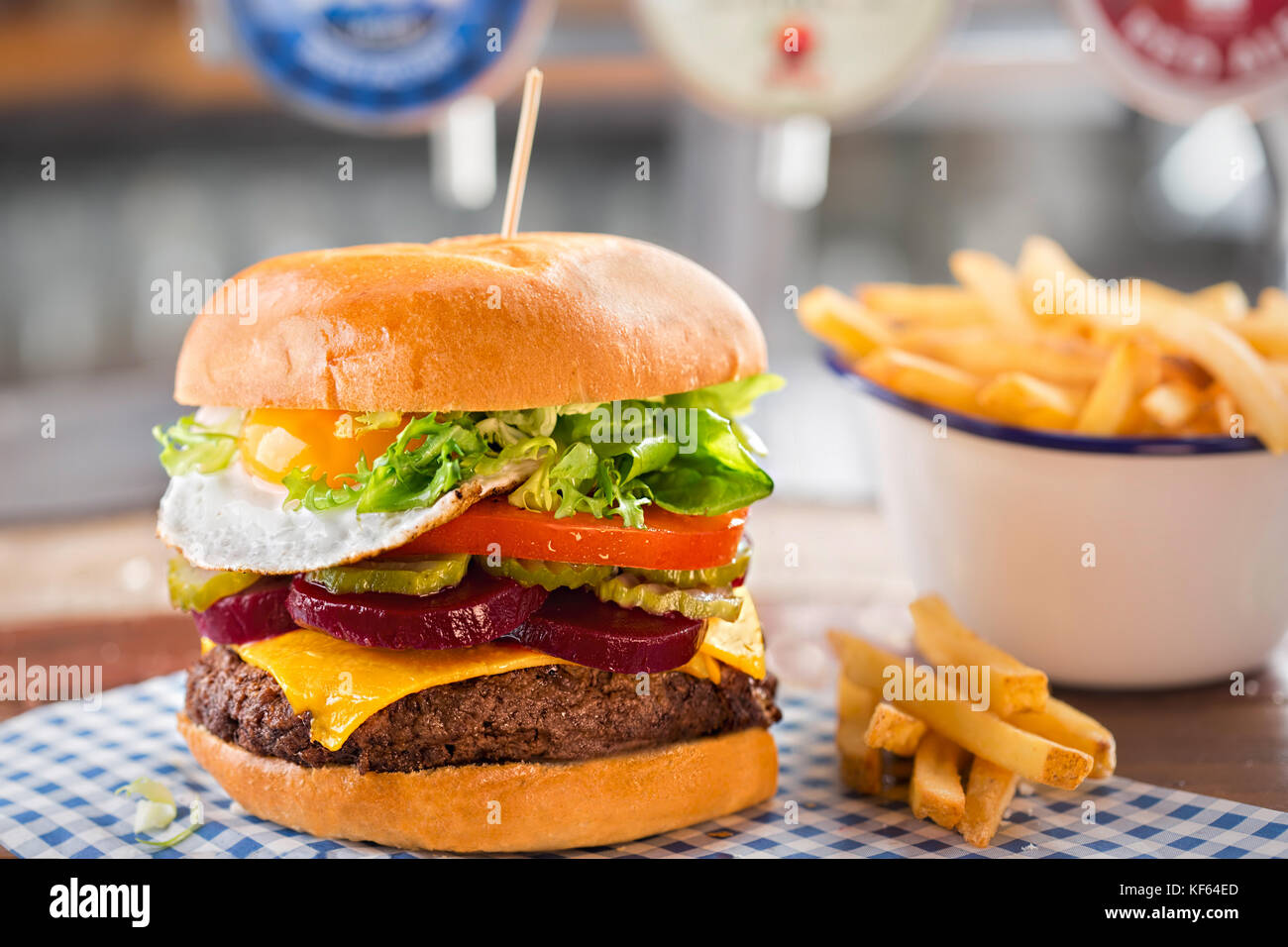 Beef burger with cheese, lettuce, tomato, beetroot & pickle, topped with a fried egg - Stock Image