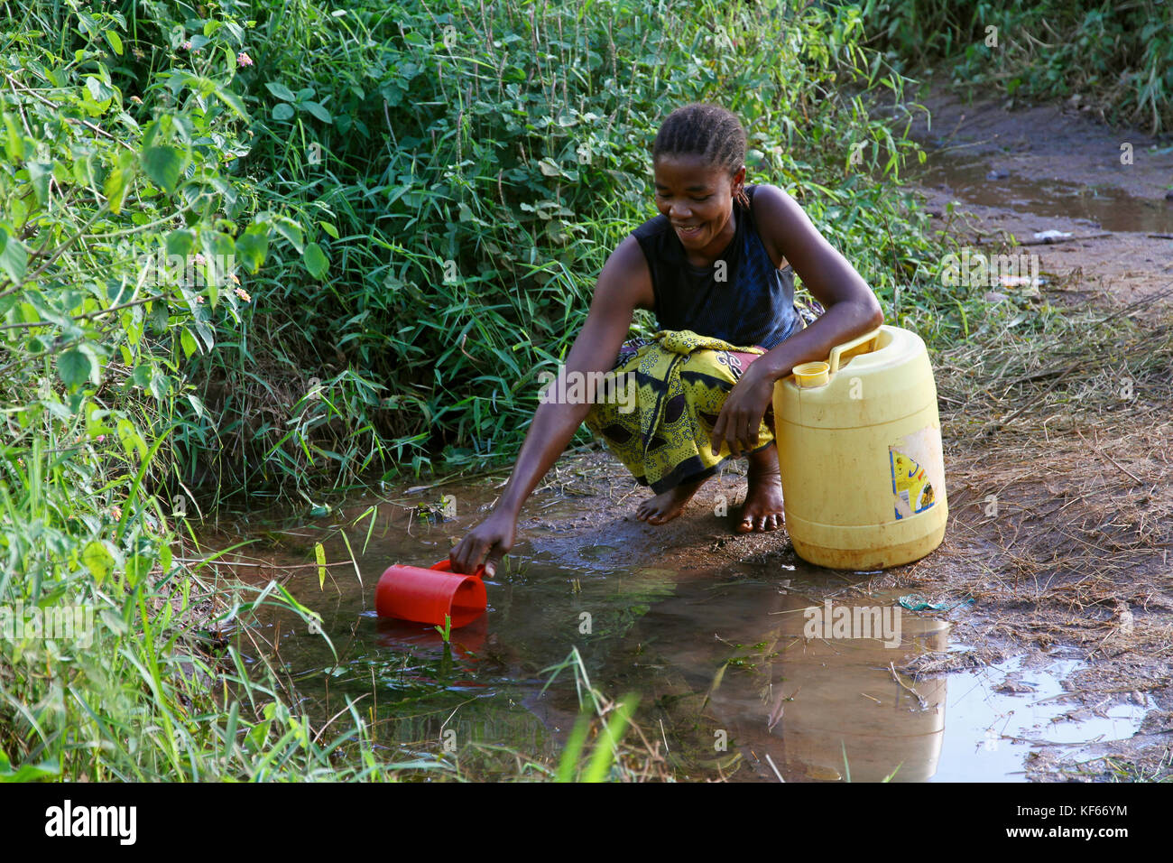 Living in the Kenya Slum Aerias - Woman collecting drinking water from source - Stock Image