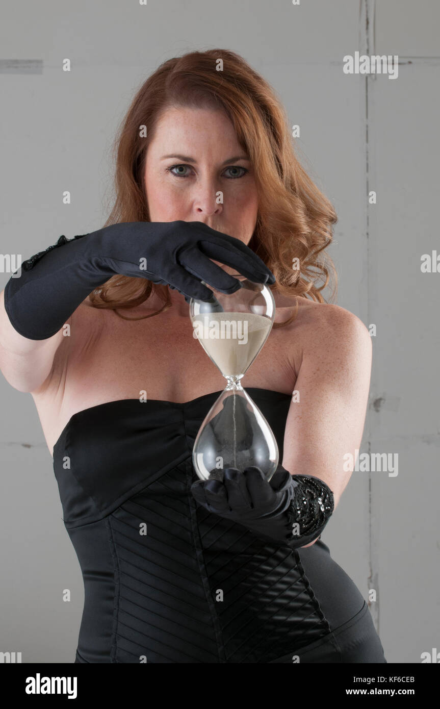 beautiful mature woman holding hourglass stock photo: 164254675 - alamy