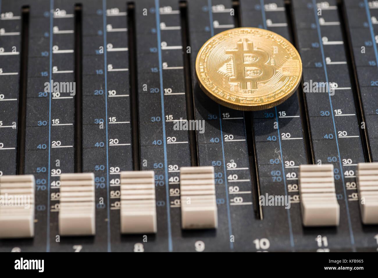 Bitcoin coin on the sound mixer console. Concept idea. Stock Photo