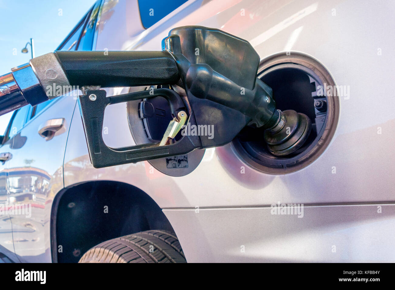 Gas pump nozzle. Petrol pump nozzle with vapor recovery. Fueling a big SUV in the US. - Stock Image