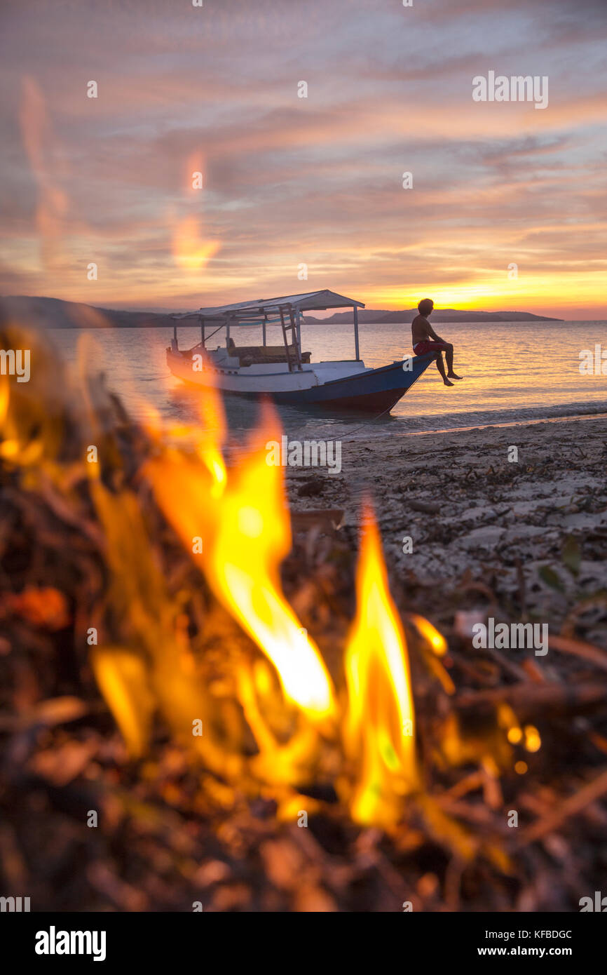 INDONESIA, Flores, Riung, view of a man enjoying the sunset, taken through a beach bonfire, Rutong island - Stock Image