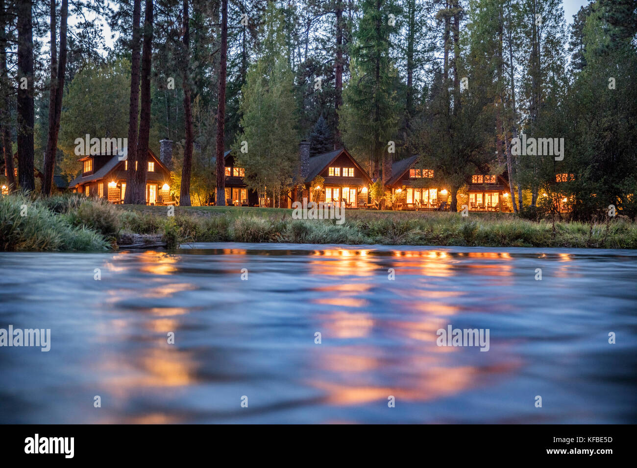 USA, Oregon, Camp Sherman, Metolius River Resort, View of cabins from River - Stock Image