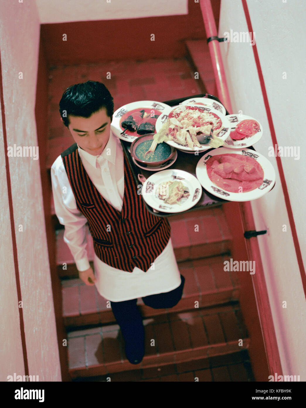 MEXICO, Mexico City, Fonda El Refugio Restaurant,  waiter moving down on staircase carrying tray of food, elevated - Stock Image