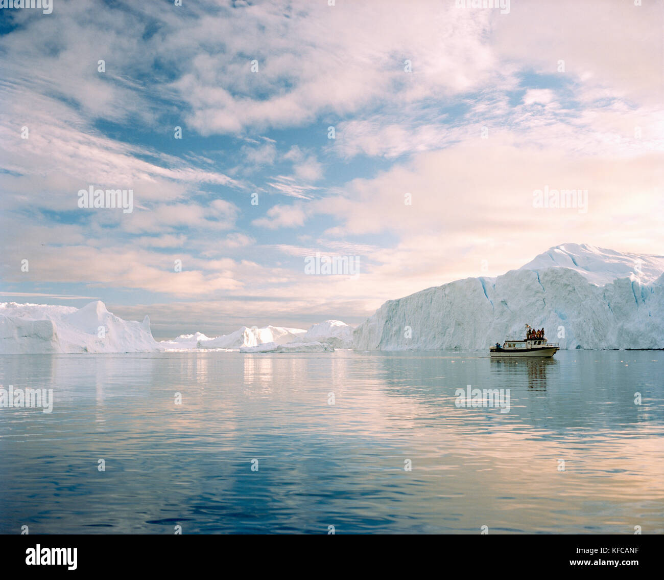 GREENLAND, Ilulissat, Ilulissat Icefjord, a tour boat during a midnight tour of the glaciers with glaciers in the - Stock Image