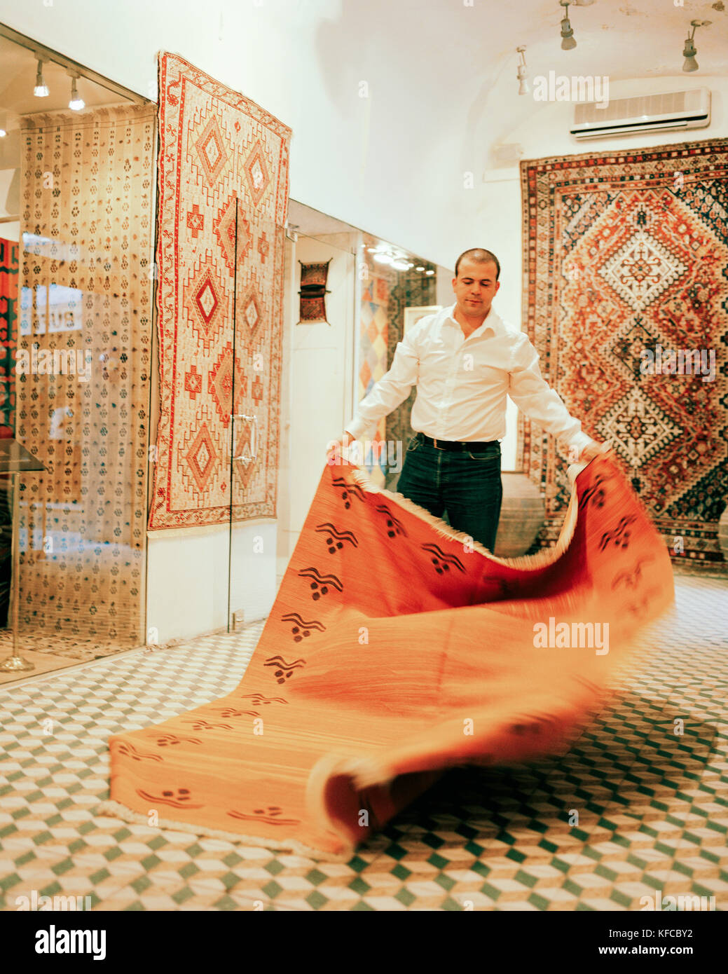 TURKEY, Istanbul, mid adult man holding Turkish carpet in his store in the Grand Bazaar. - Stock Image