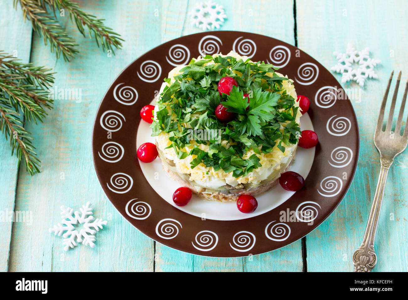 Homemade snacks on a festive Christmas table. Fish salad with mushrooms, salmon, cranberries and cheese. - Stock Image