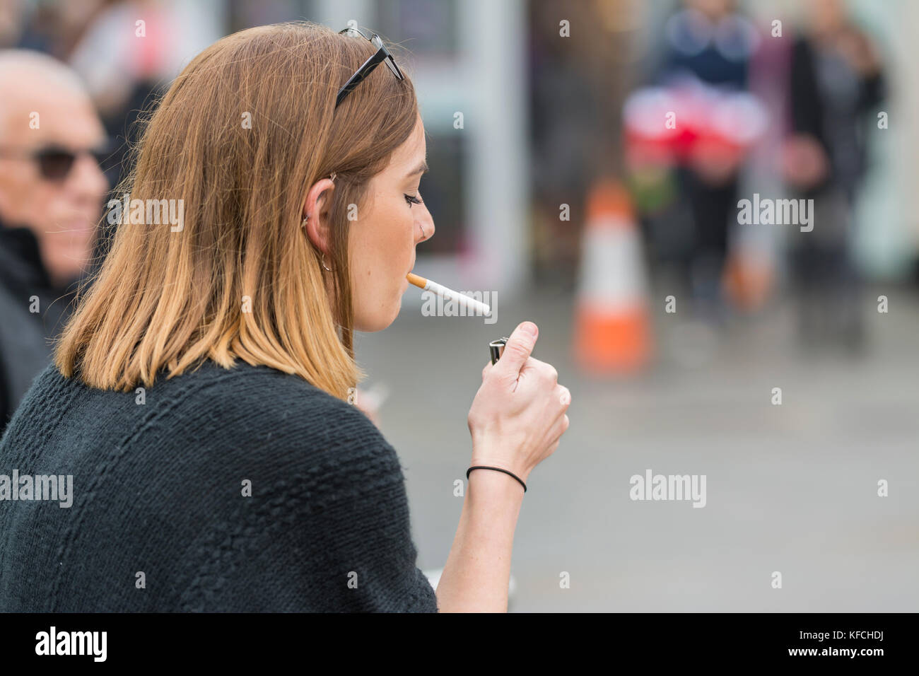 Young woman lighting a cigarette in the UK. Unhealthy lifestyle Stock Photo: 164390286 - Alamy
