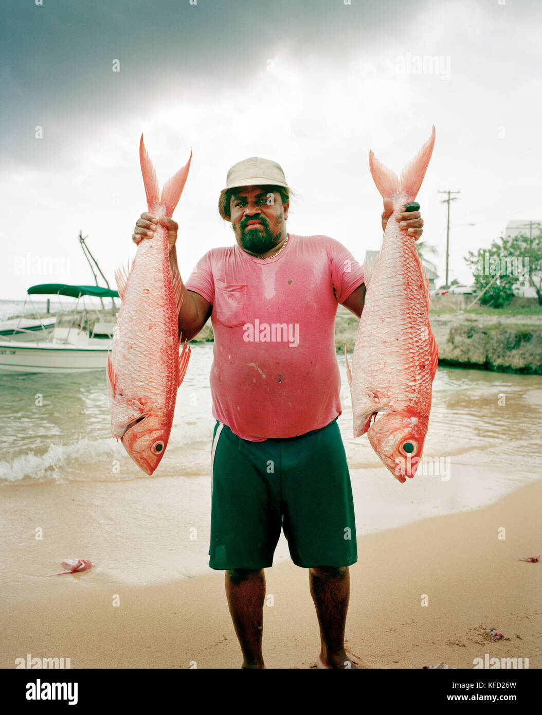 CAYMAN ISLANDS, Grand Cayman, fisherman holding two red snapper caught in the Caribbean Sea - Stock Image