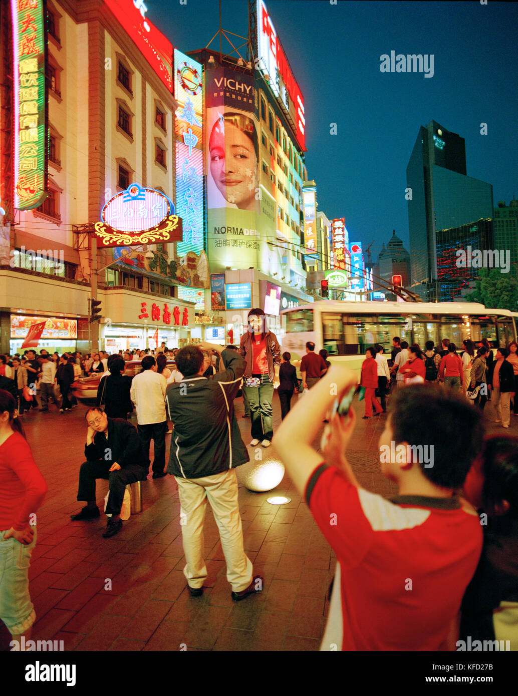 CHINA, Shanghai, people take photos of one another on a busy urban shopping street - Stock Image