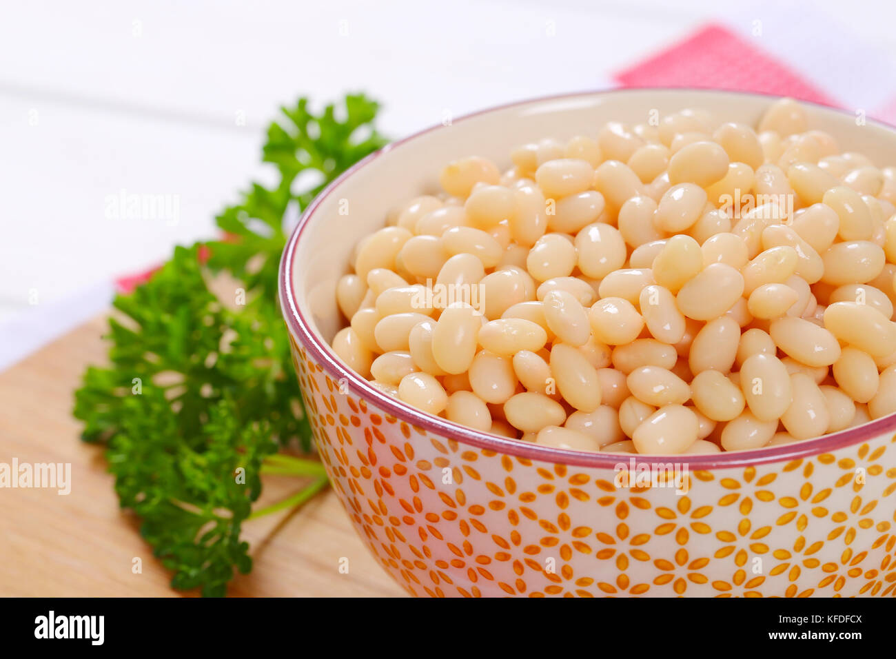 bowl of canned white beans on wooden cutting board - close up - Stock Image