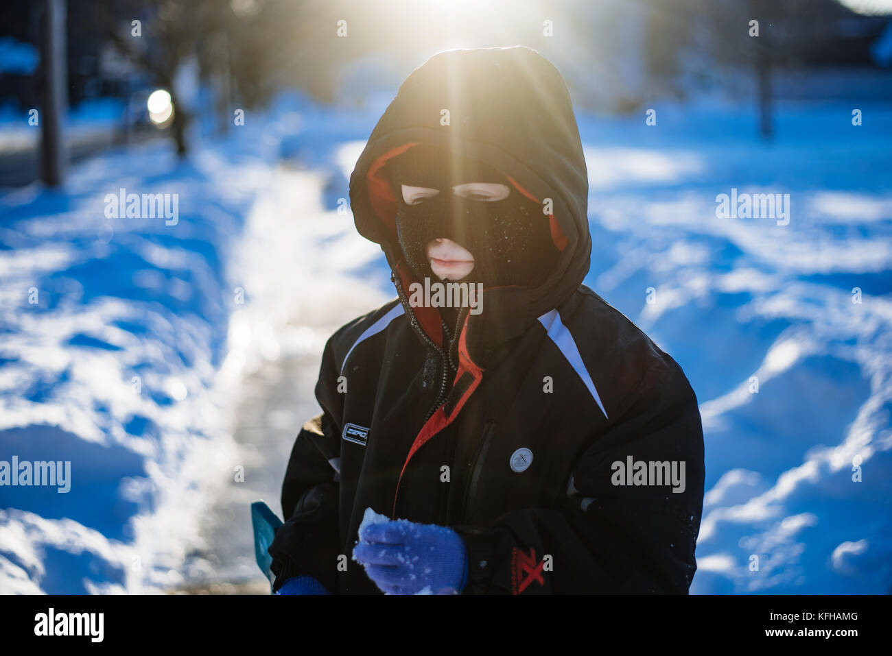 10-11 year old boy standing in snow with ski mask - Stock Image