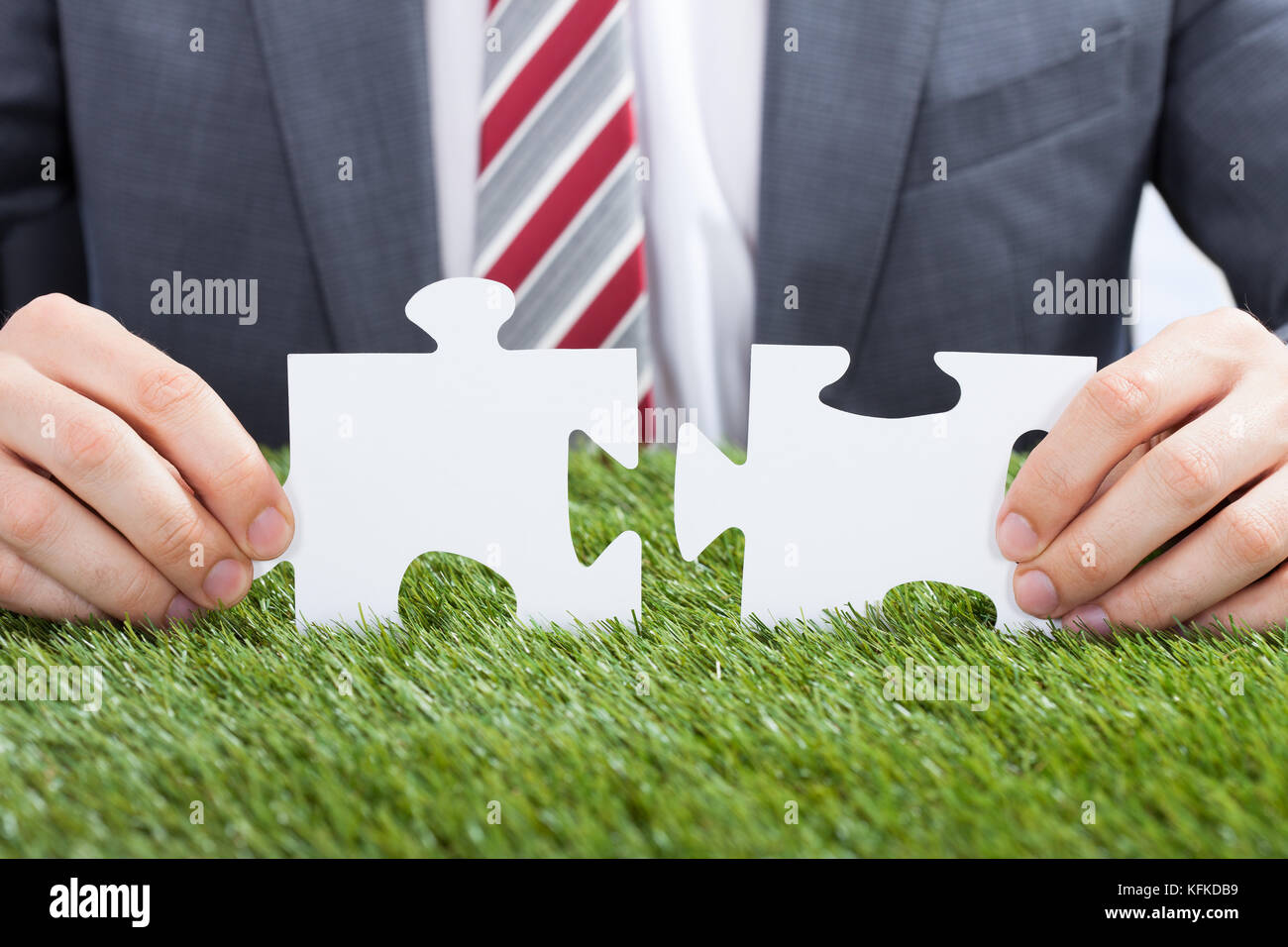 Closeup of businessman joining puzzle pieces on grass - Stock Image