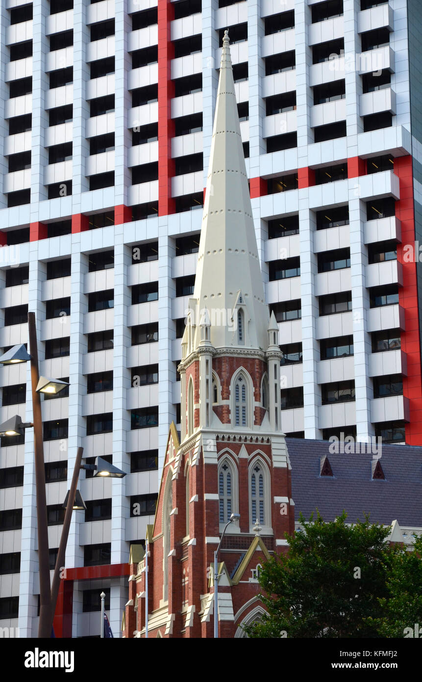 The Albert Street Uniting Church in Brisbane, Australia set against a modern skyscraper behind. - Stock Image