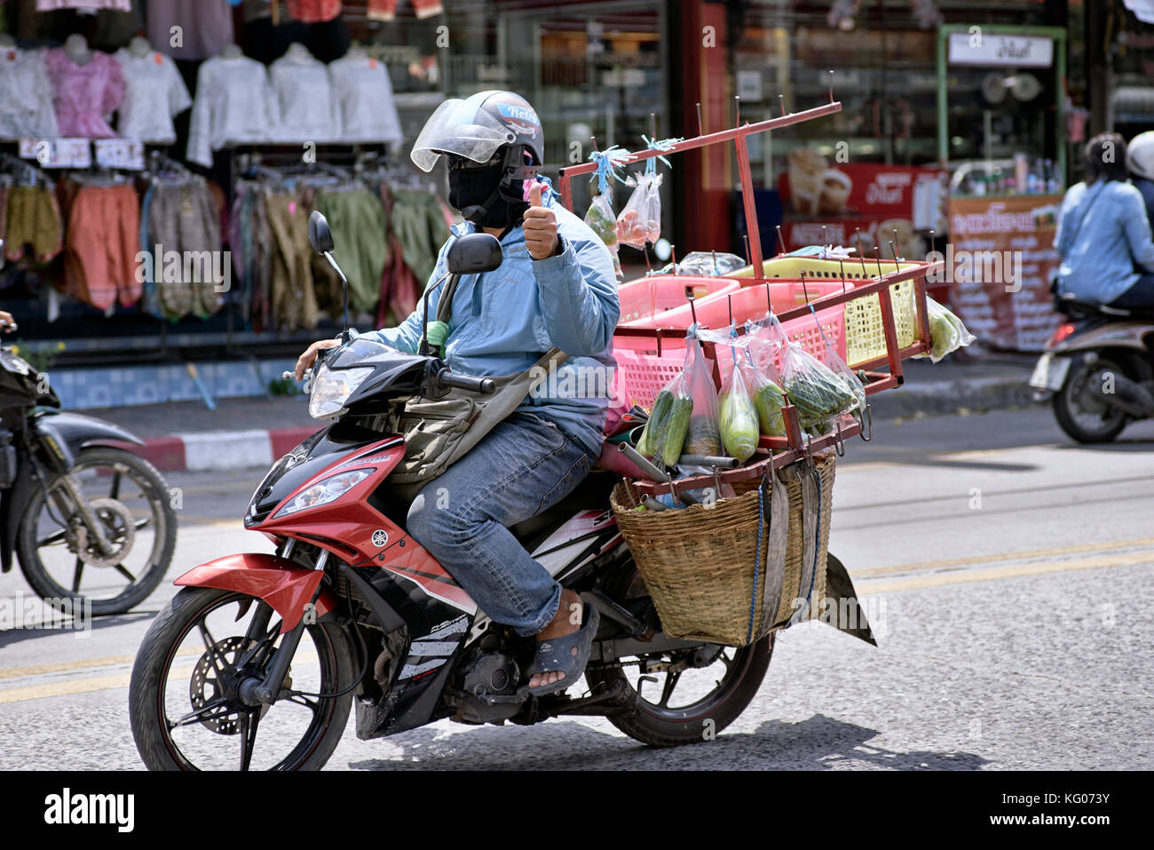 Thailand street food vendor delivering food on his motorcycle. Southeast Asia. - Stock Image