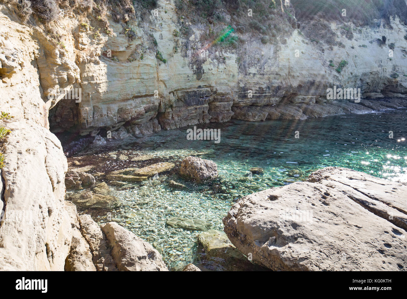 Rocks by the Ionian Sea, Corfu, Greece, cristal clear blue or turquoise sea water, holidays, vacation in the mediterranean - Stock Image
