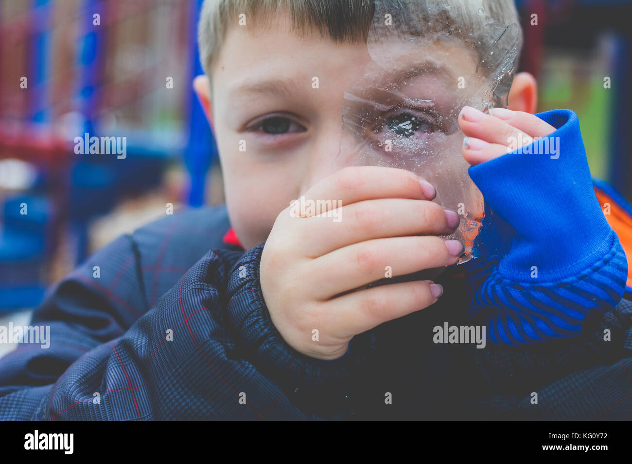 Boy looking through a piece of ice in winter - Stock Image