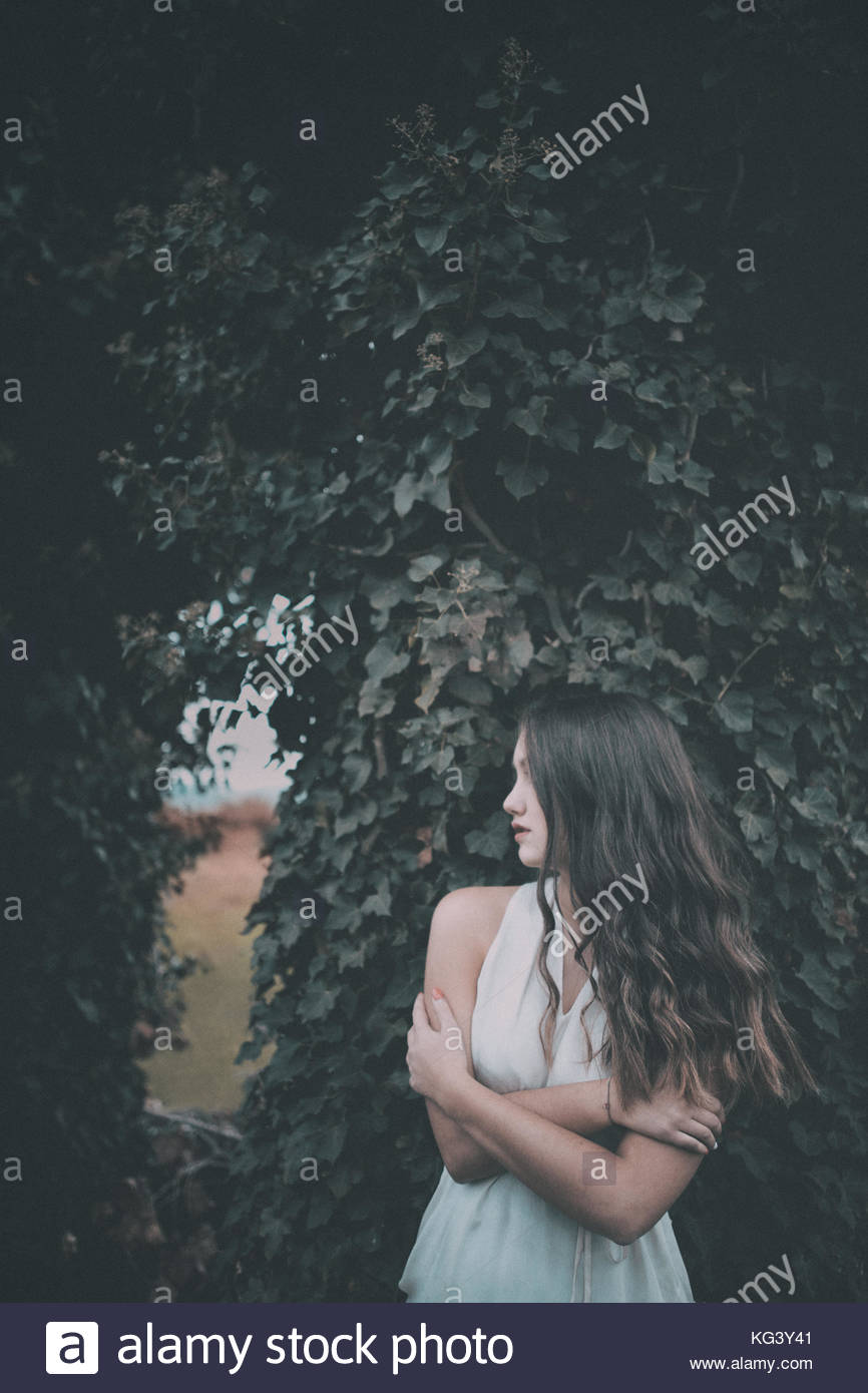 Girl near a tree covered in ivy, in a white dress, in fear - Stock Image