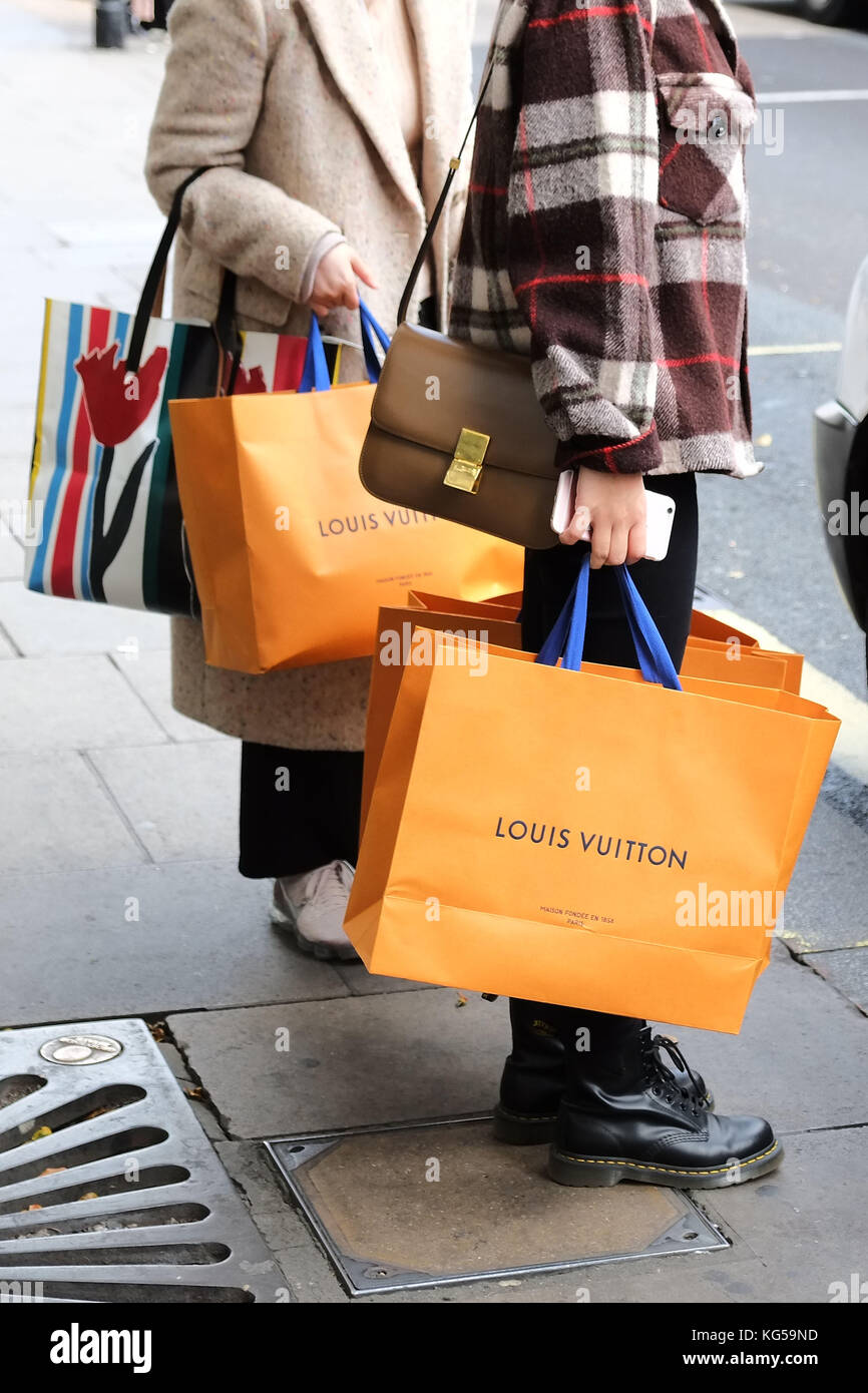 Designer shopping on Oxford Street, shoppers hail a cab after spending thousands of Pounds / Dollars /Yen etc at - Stock Image