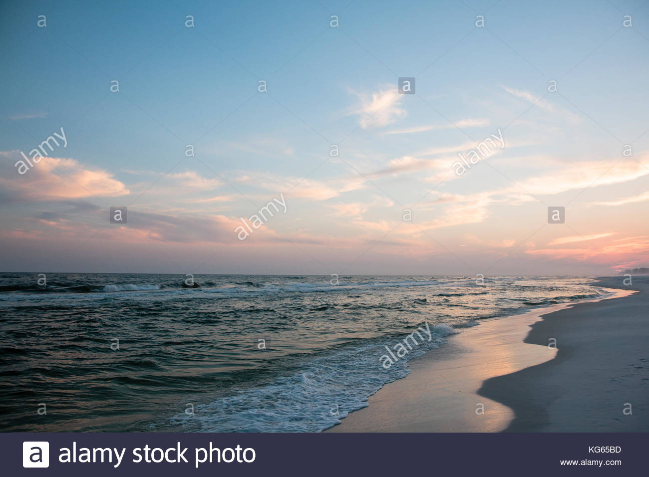 The evening sun has set in the west beyond the distant commercial buildings along the gulf shores just west of TopsailStock Photo