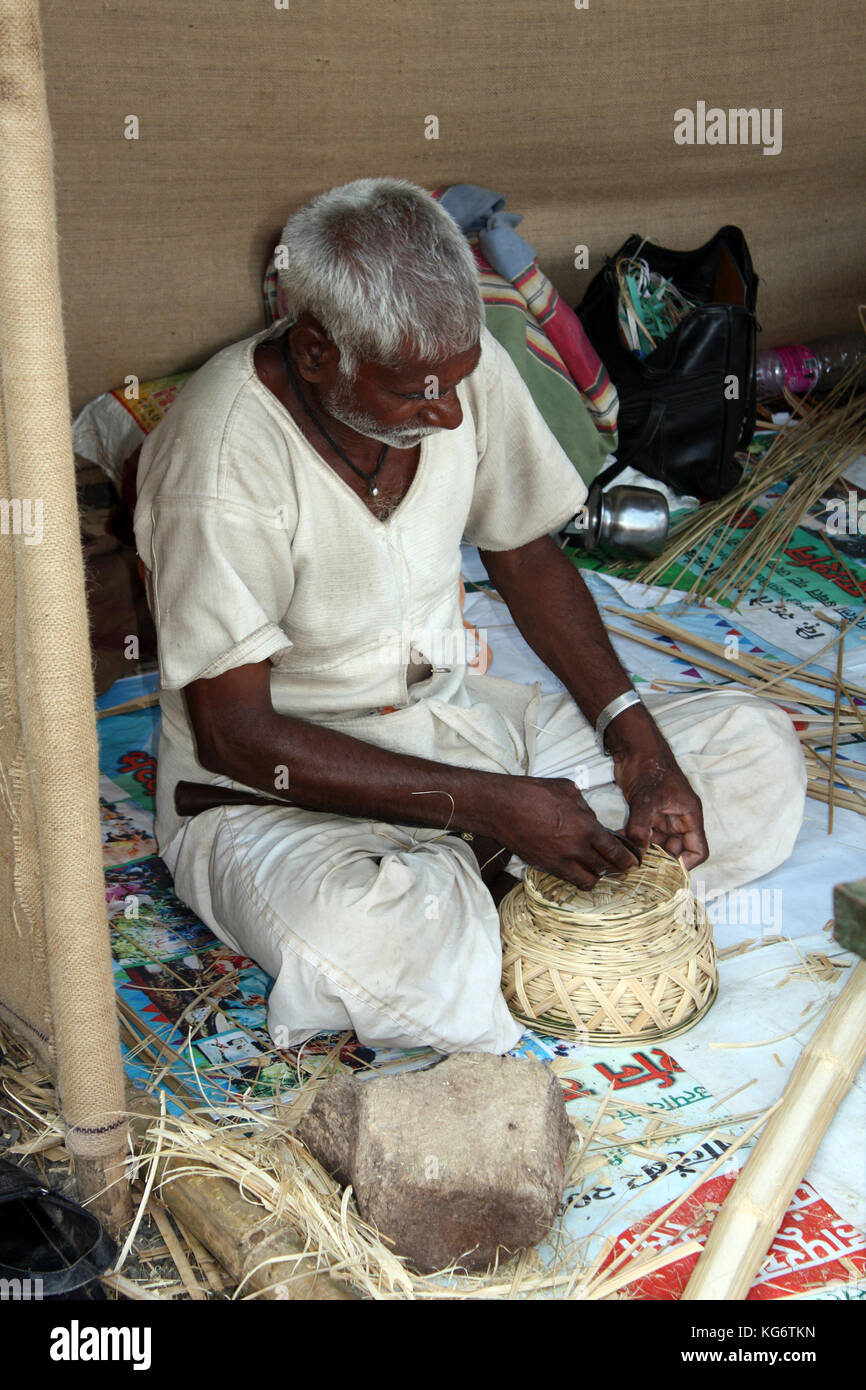 A craftsman makes cane basket in his handicraft workshop in India. - Stock Image