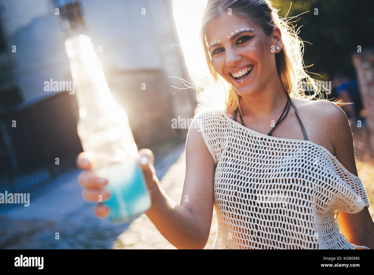 Portrait of happy young girl holding drink - Stock Image