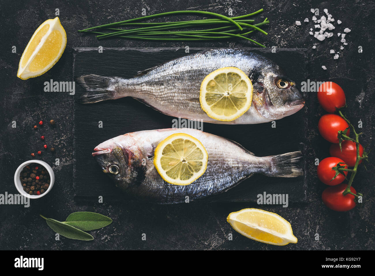 Fresh sea beam or dorado fish, lemon, herbs, spices and vegetables on black stone slate background. Top view. Fresh - Stock Image