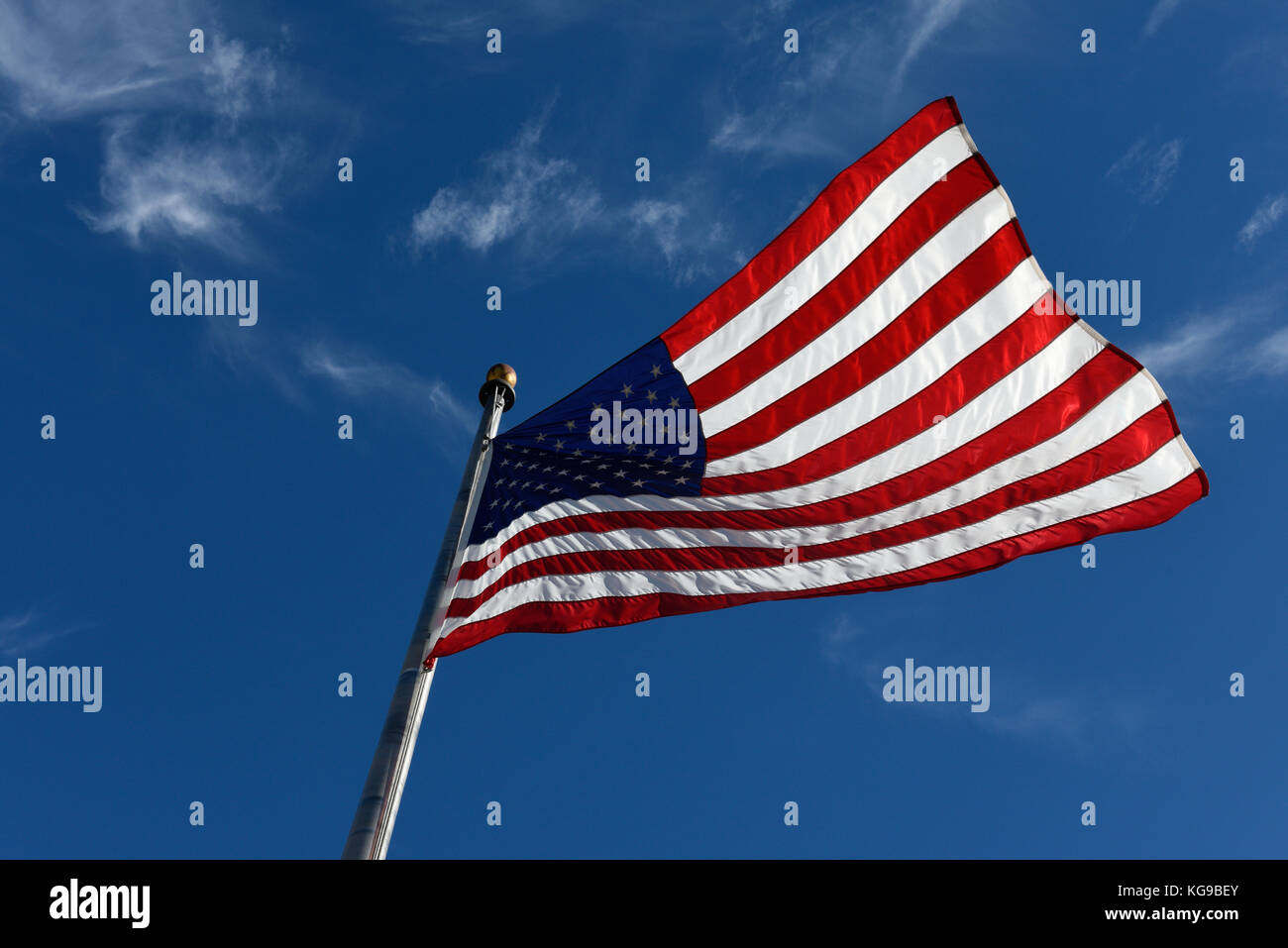 The American Flag Flying, Stars and Stripes,  United states of America Flag Blue sky. The Star-Spangled Banner USA - Stock Image