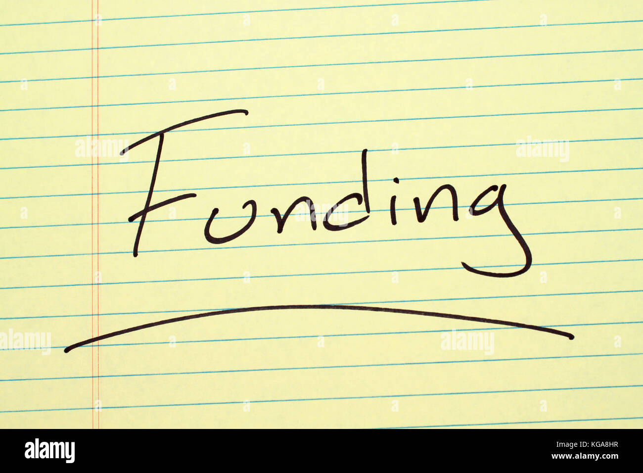 The word 'Funding' underlined on a yellow legal pad - Stock Image
