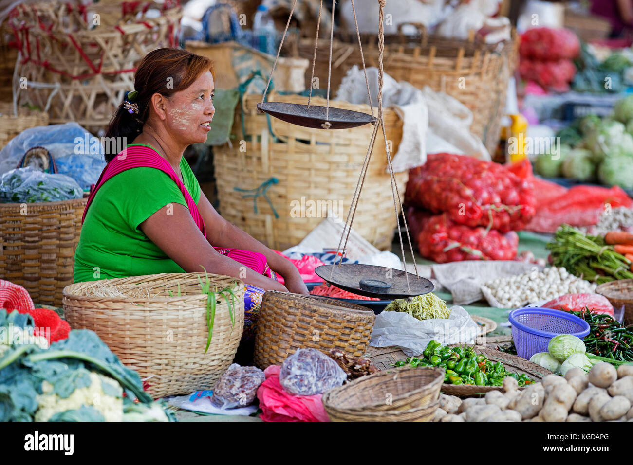 Burmese woman wearing thanaka on her face selling vegetables at food market in village along Inle Lake, Nyaungshwe, - Stock Image