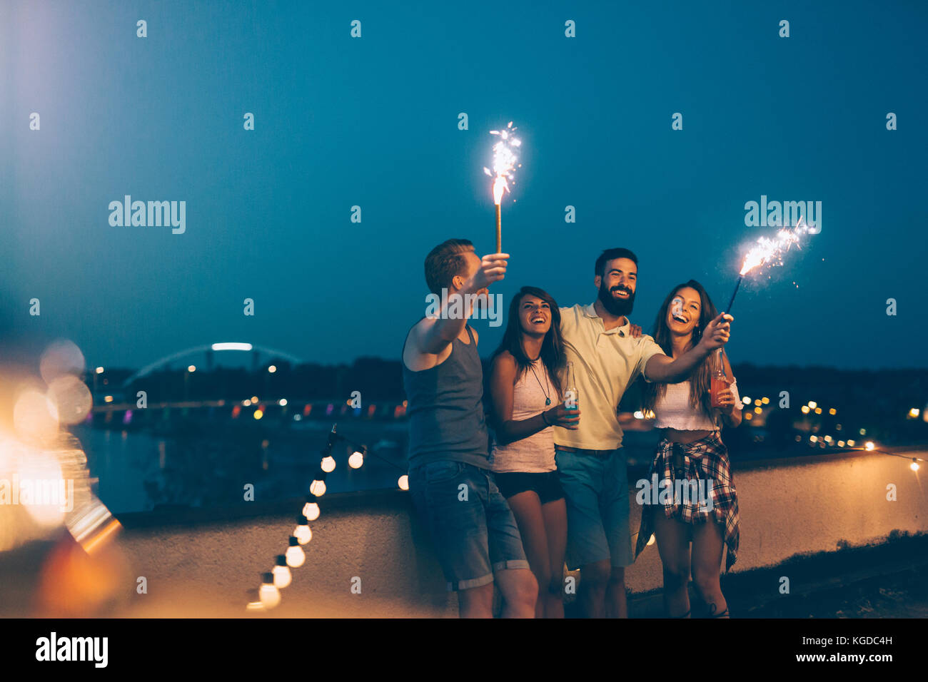 Group of happy friends celebrating at rooftop - Stock Image