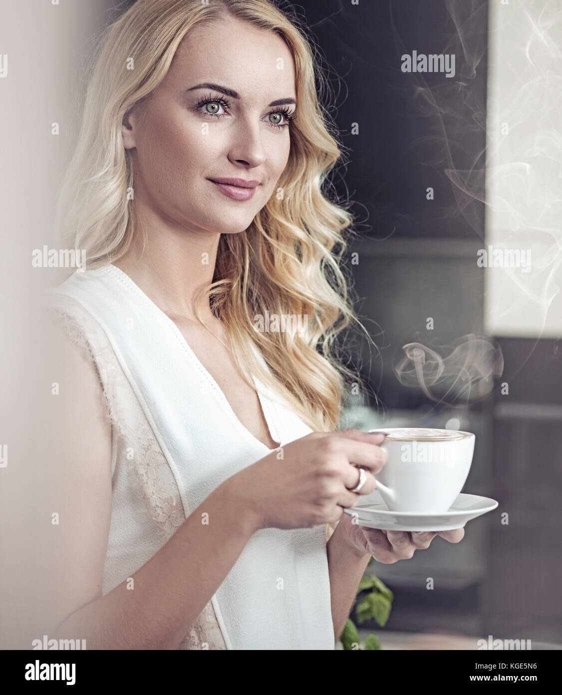 Portrait of a pretty blond lady drinking a cup of coffee - Stock Image