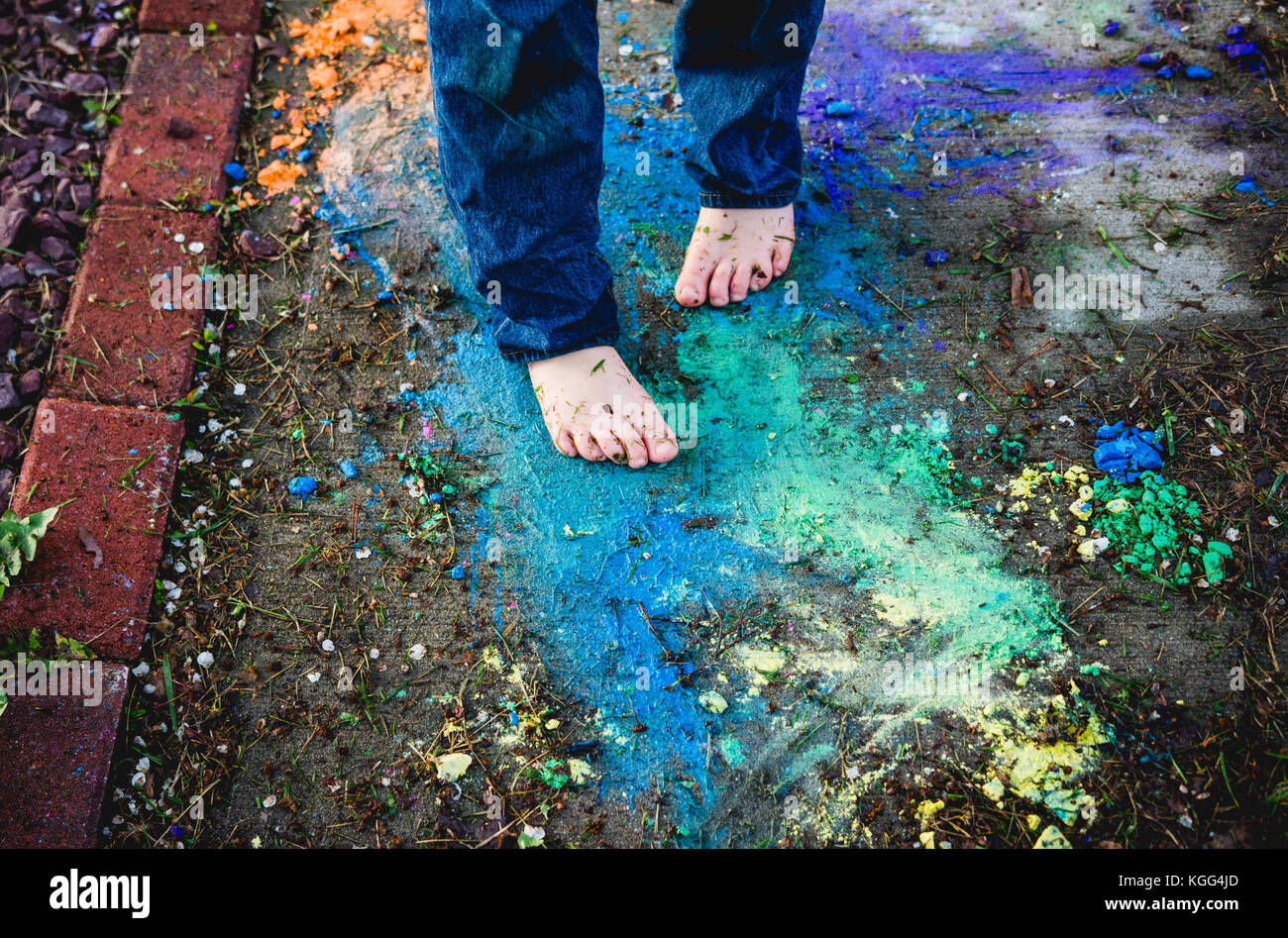 A child stands barefoot on a sidewalk with colors around the feet - Stock Image