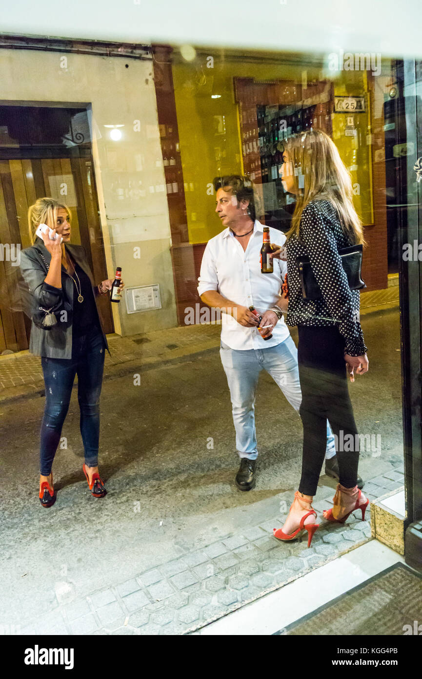 two-women-in-high-heels-and-a-man-drinking-beer-and-smoking-in-the-KGG4PB.jpg