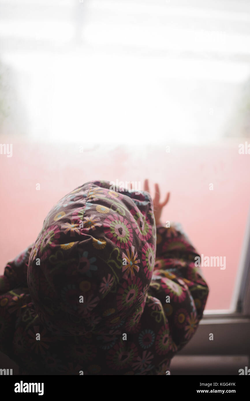 A little girl looks out a window at cold weather - Stock Image